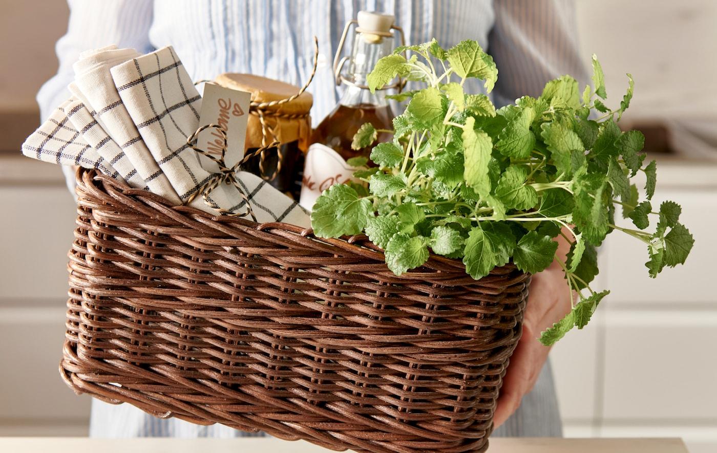 Ręce osoby wręczającej kosz GABBIG z przewiązanymi wstążkami ręcznikami kuchennymi, domowymi przetworami w szklanych słoikach i świeżymi ziołami.