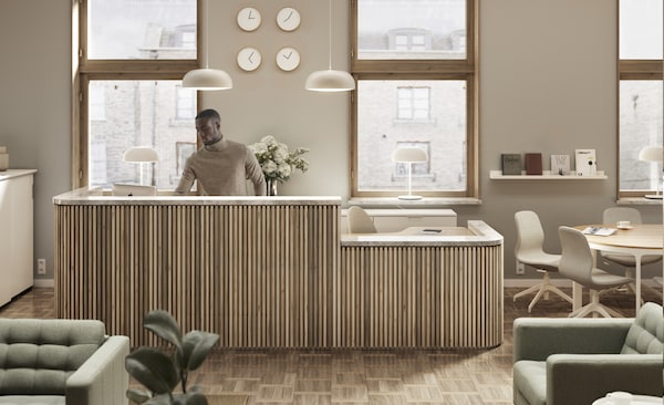 Reception area in beige and light-wood color scheme. Man is standing behind the desk and windows overlook the city scape.