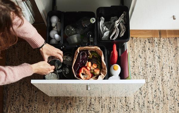 Reciclaje clasificado en cajas de plástico dentro de un cajón abierto.