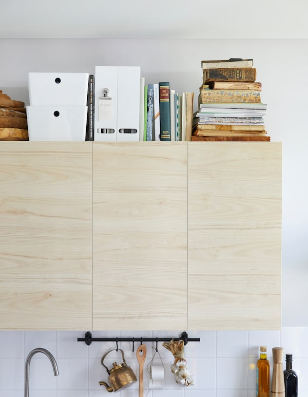 Recipe books and storage boxes on top of birch kitchen wall cabinets.