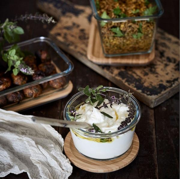 Recipientes para alimentos em vidro IKEA 365+ com tampas de bambu com diferentes conteúdos, sobre uma superfície escura de madeira.
