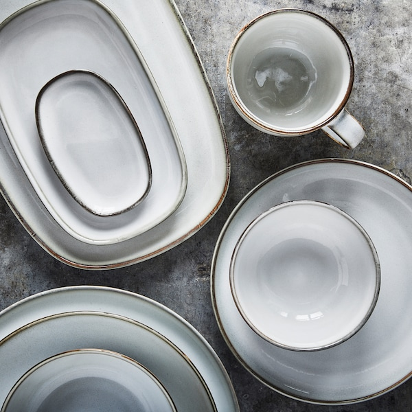 Recipientes, platos y elementos de vajilla en gris claro en tres pilas con una taza al lado sobre una superficie gris.