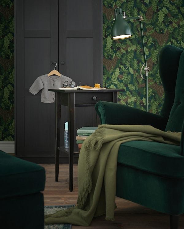 Recuncho de lectura cunha cadeira de brazos verde, unha lámpada de pé verde e unha mesiña de noite HEMNES a modo de mesa auxiliar.
