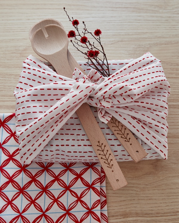 Red and white VINTERFEST kitchen towels wrapped around utensils and a sprig with flowers.