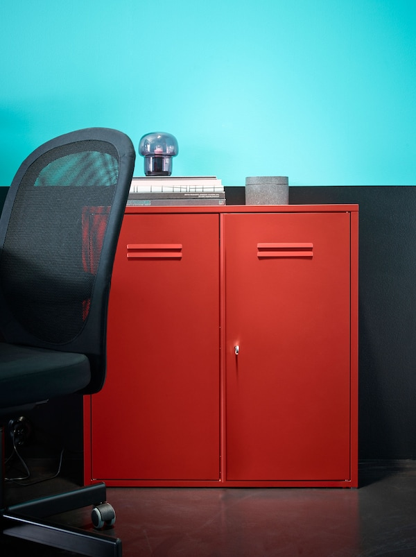 Red IVAR cabinet with doors in front of a turquoise and black wall, with a black FLINTAN chair beside it.