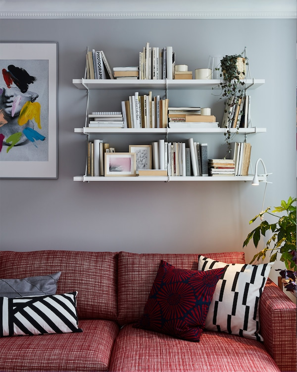 Red sofa with white and red patterned decorative cushions. White shelves are mounted on the wall behind and store books.