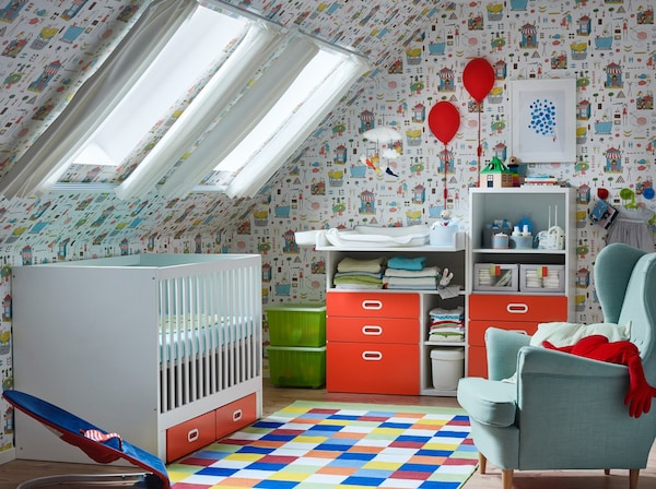 Red, turquoise and white nursery with a red and white STUVA/FRITIDS cot with drawers, changing table and bookcase.