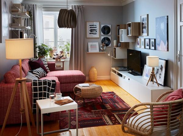 レッドのペルシャ模様のラグ、レッドのソファ、グレーのカーテン、籐製アームチェア、ムード照明がある小さなリビングルーム。