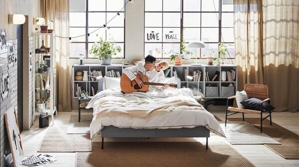 Redécouvrez votre maison, mari et femme avec une guitare dans un lit de lin blanc
