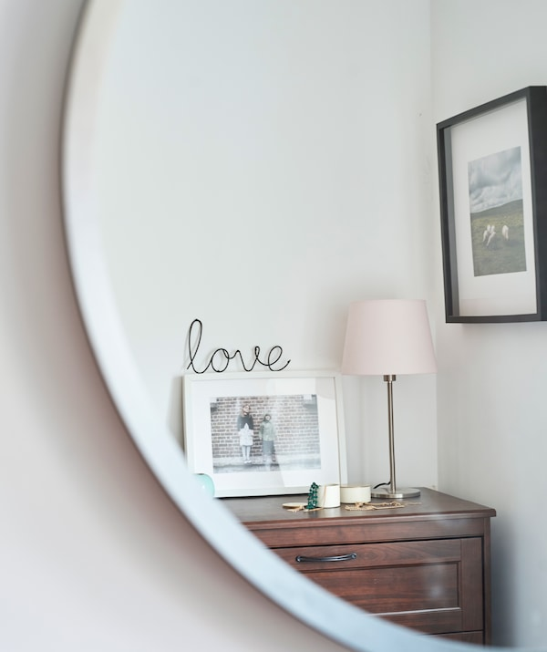 Reflection of a chest of drawers with a photo frame displayed on top, next to a pink and brass table lamp and trinket boxes.