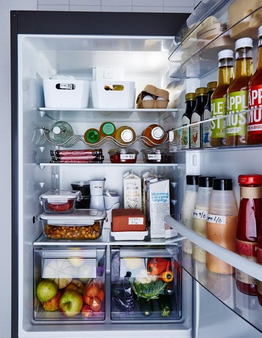 Réfrigérateur bien ordonné et aliments rangés dans des contenants transparents ou étiquetés.