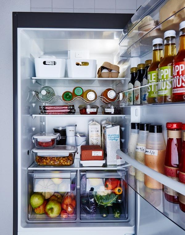 Réfrigérateur bien rangé avec aliments rangés dans des boîtes transparentes ou étiquetées.