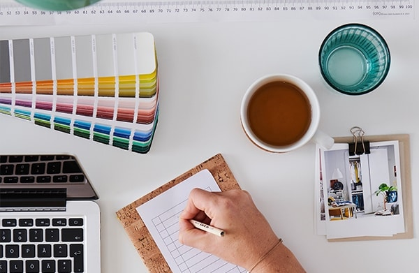 Register your interest for free message with an image. A white desk with a laptop, cup of coffee, glass of water, a pencil organiser cup, a desk light and a customer writing notes on the desk to get ready for an online planing service from home.