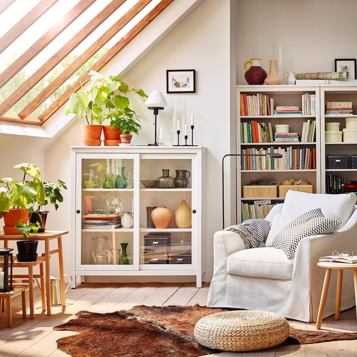 Reilun kokoinen ja mukava valkoinen IKEA FÄRLÖV-nojatuoli ja HEMNES-vitriinikaappi valkoisessa olohuoneessa, jossa on lasinen taitekatto.