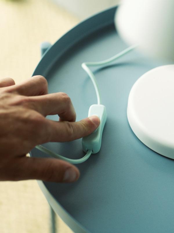 Ręka osoby naciskającej wyłącznik białej lampy stołowej ustawionej na jasnoniebieskim stole.