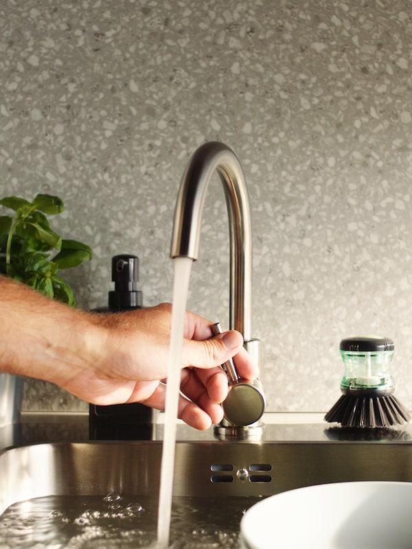 Ręka osoby regulującej strumień wody płynącej z wykonanej ze stali nierdzewnej baterii kuchennej GLYPEN, obok której leży szczotka do mycia naczyń TÅRTSMET.