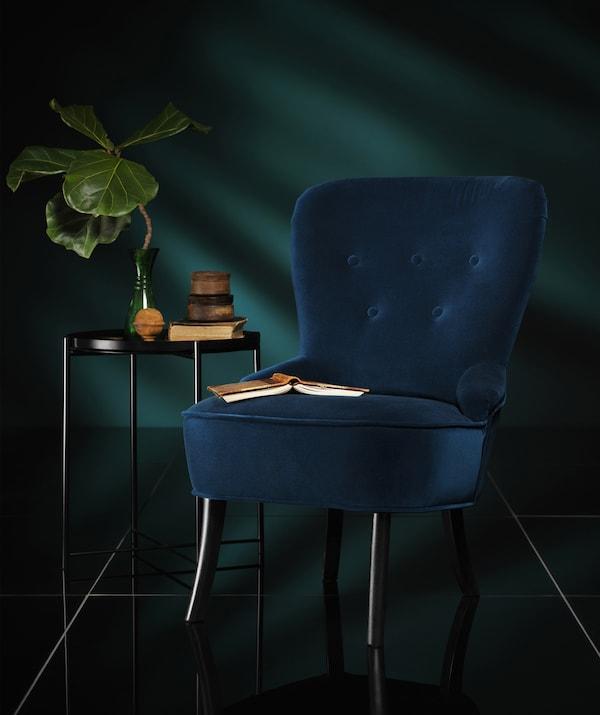 """REMSTA Sessel mit Bezug """"Djuparp"""" dunkel grünblau in einem dunklen Raum"""