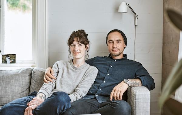 Rena und Sam sitzen in ihrem Bauernhaus auf einer Couch.