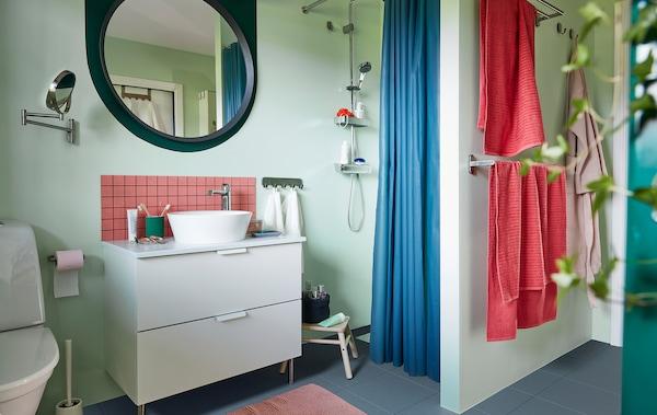 Rendezett fürdőszoba, lágy pasztellszínekkel, mosdóállvány, zuhany, törölközősín, tükör, növények és kiegészítők.