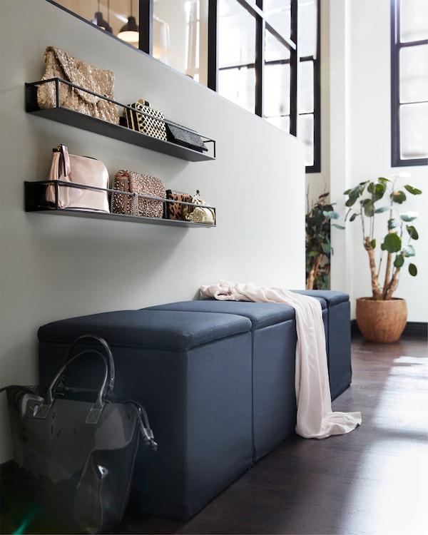 Repose-pieds à rangement intégré noirs, étagères murales noires et plante d'intérieur