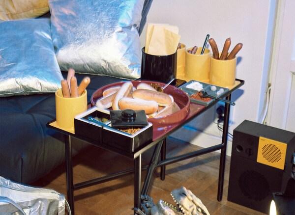 Repousa-pés preto com duas almofadas prateadas e uma mesa de apoio com louça modular com salsichas e pães para cachorro.