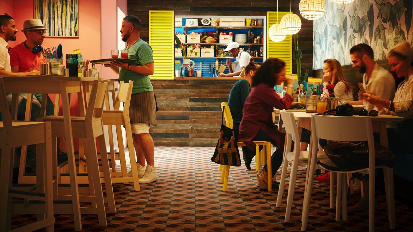 Restaurante pequeño con mesas altas NORRÅKER blancas de abedul, taburetes altos de abedul, lámparas de techo de bambú y algunos clientes.