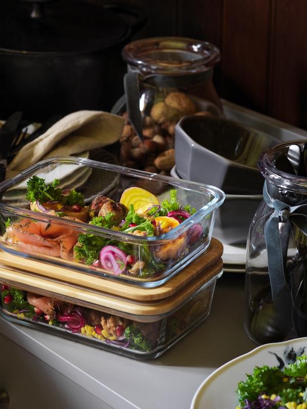 Resztki łososia z warzywami przełożone do dwóch ustawionych na sobie pojemników IKEA 365+ z bambusowymi pokrywkami.