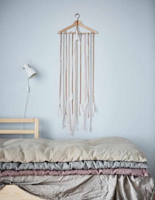 Retales de tela largos con plumas colgados de una percha de madera BUMERANG en un pared: decoración casera en estado puro.