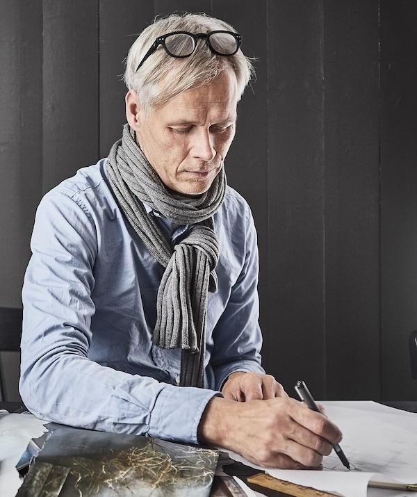 Retrato de Hans Blomquist dibujando un boceto sobre una mesa.