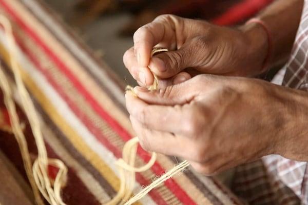 Retrato de una mujer confeccionando una alfombra a mano.