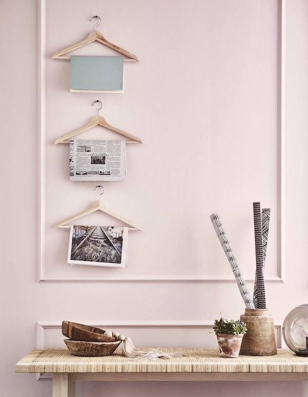 Revistas colgadas en tres perchas de madera BUMERANG en una pared.