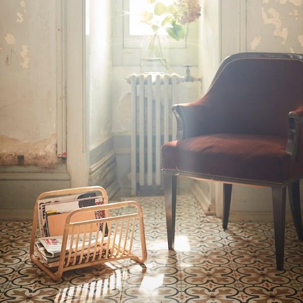 Revisteiro artesanal BUSKBO de ratán natural con varias revistas no seu interior ao carón dunha cadeira de brazos.