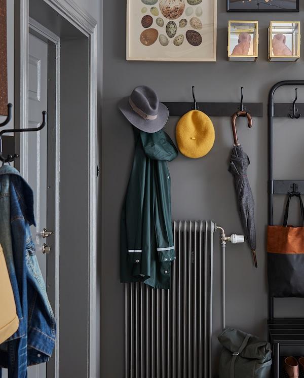 رف أسود مع ثلاثة خطافات مثبت على الحائط فوق المدفأة. مظلة، واثنتان من القبعات وسترة شتوية معلقة على خطافات.
