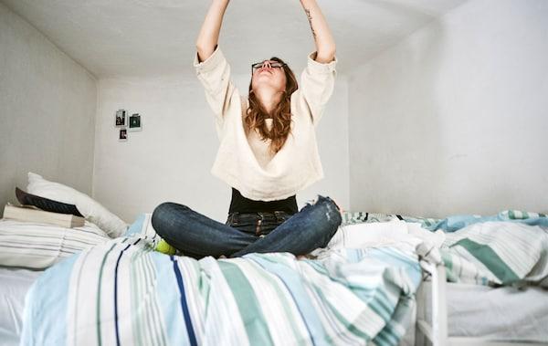 Rhianna încercând să ajungă la ceva de pe patul ei la mezanin.