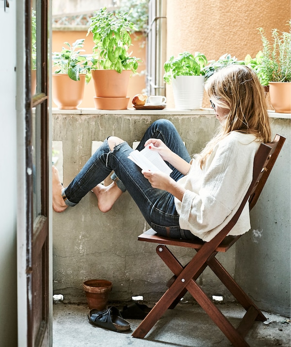 Rhianna sitting on a foldaway wooden chair and reading on her outside balcony lined with plants in pots.
