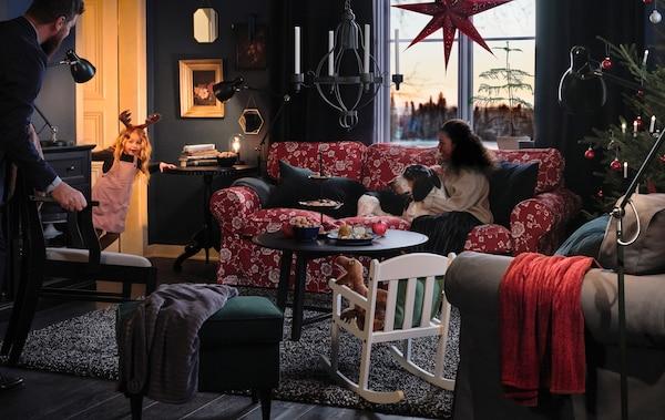 リビングルームでくつろぐ家族と愛犬が、部屋のドアから覗き込む少女がショーを披露するのを待っている。