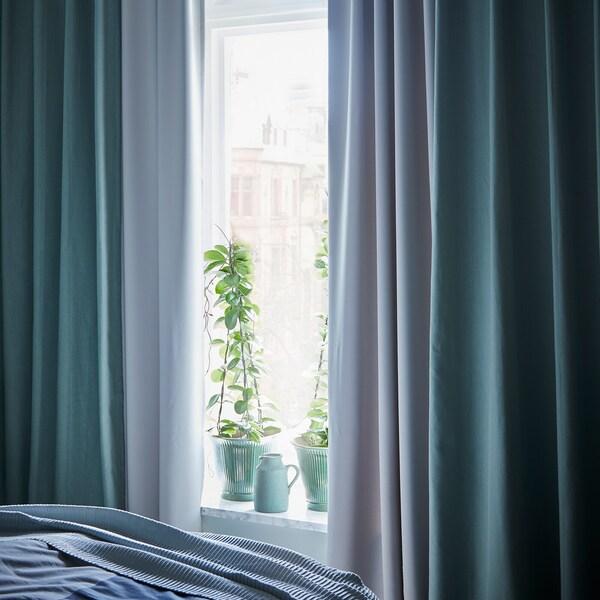 Rideaux turquoise foncé encadrant une fenêtre ensoleillée, dans une chambre à coucher.