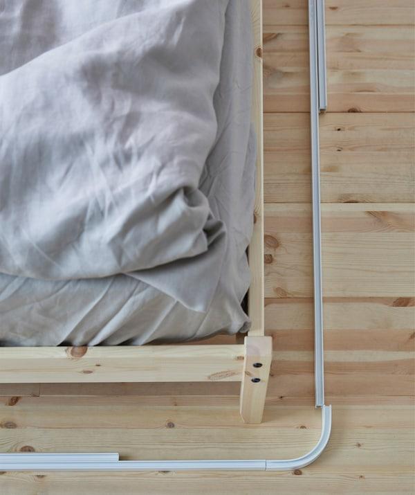 Rieles de cortina VIDGA sobre el suelo alrededor de una cama para medirlos antes de su instalación