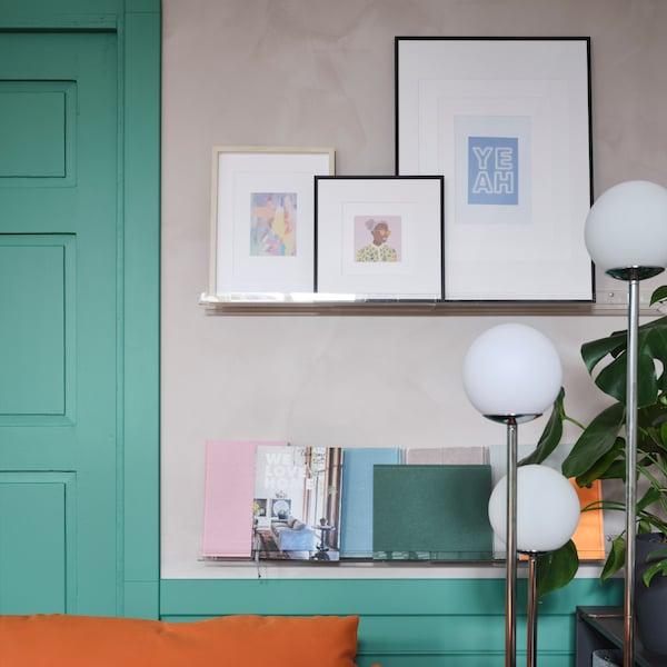 壁取り付け型の透明アート用飾り棚に、フレーム入りアート、ポスター、本、パステルカラーのノートが飾られています。