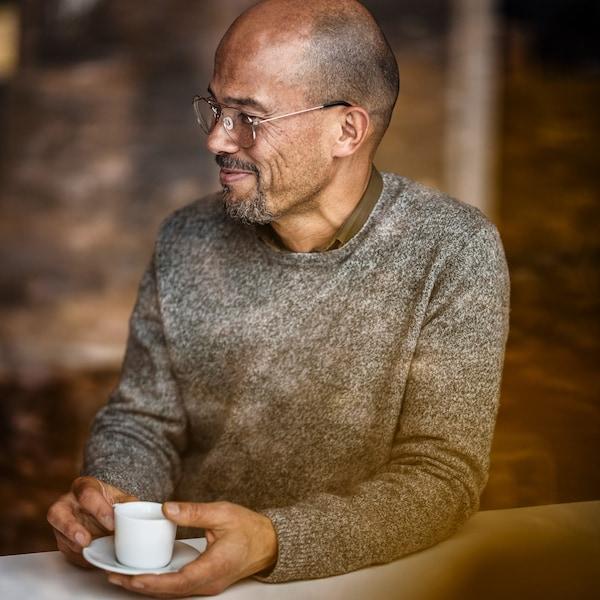 رجل في منتصف العمر مبتسميرتدي نظاراتويستمتع بشرب القهوة.
