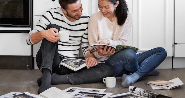 رجل وامرأة يجلسان على أرضية مطبخ يطالعان كتالوج ايكيا.