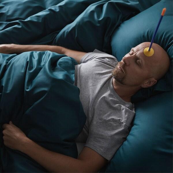 رجل ينام في سرير فاخر، مع سهم بلاصقة مطاطية ملتصق بجبهته.