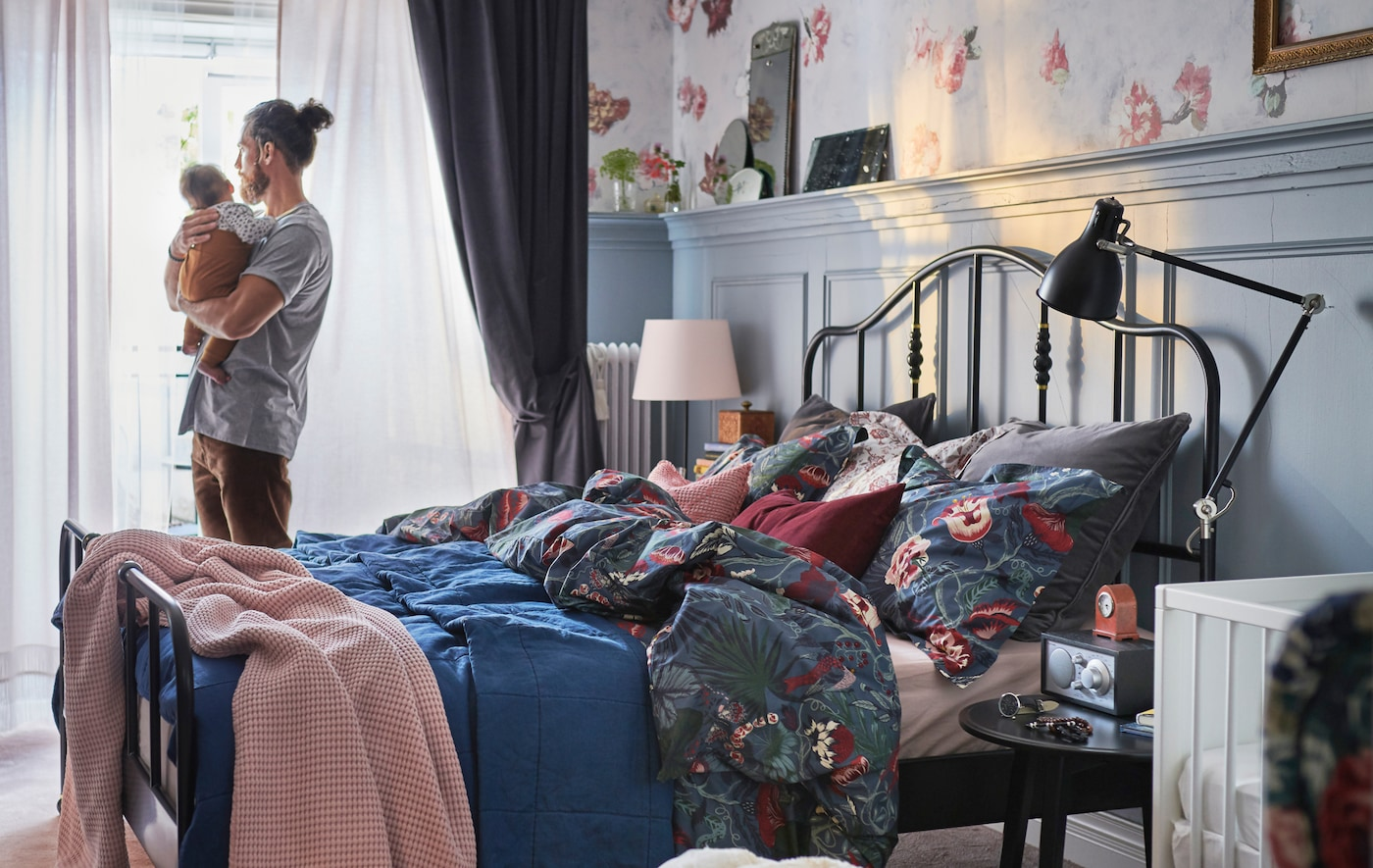 رجل يقف حاملًا طفل رضيع في غرفة نوم مع مفروشات سرير مزركشة زهور وطبقات ستائر على النافذة.