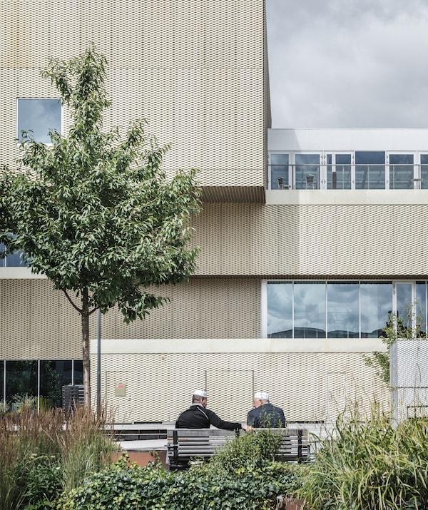 رجلان جالسان على مقعد في حديقة خارج مبنى مغطى بالمعدن الذهبي.
