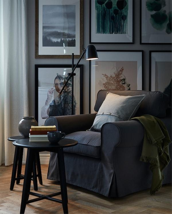 ركن للقراءة مع كرسي بذراعين كبير وناعم وضوء للقراءة وكتب على طاولة قهوة والجدار خلفها مغطى بالأعمال الفنية.