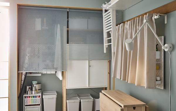ركن من غرفة مع إكسسوارات للهوايات في وحدات تخزين IVAR خلف ستائر عاتمة وطاولة NORDEN وعلى لوحة مشابك مدلاة.