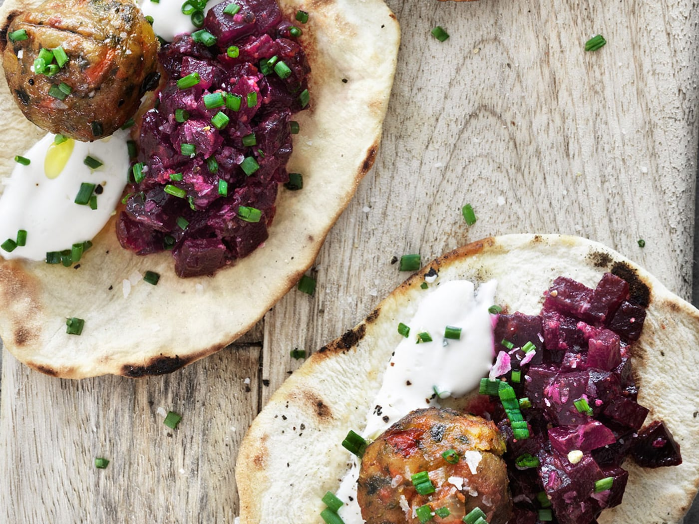 Roasted beet relish and veggie balls on naan bread garnished with yoghurt and chopped chives, served on a wooden board, seen from above.