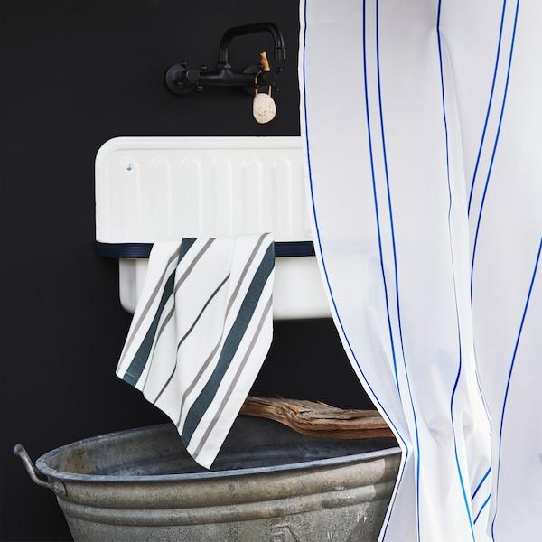 Robinet noir, lavabo blanc, serviette et rideau de douche rayés, et seau en métal placé au sol.