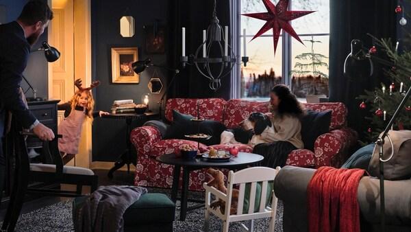 Rodina a její pes sedí v obývacím pokoji, čekají na malou holčičku, vykukující ze dveří, aby předvedla svou show.