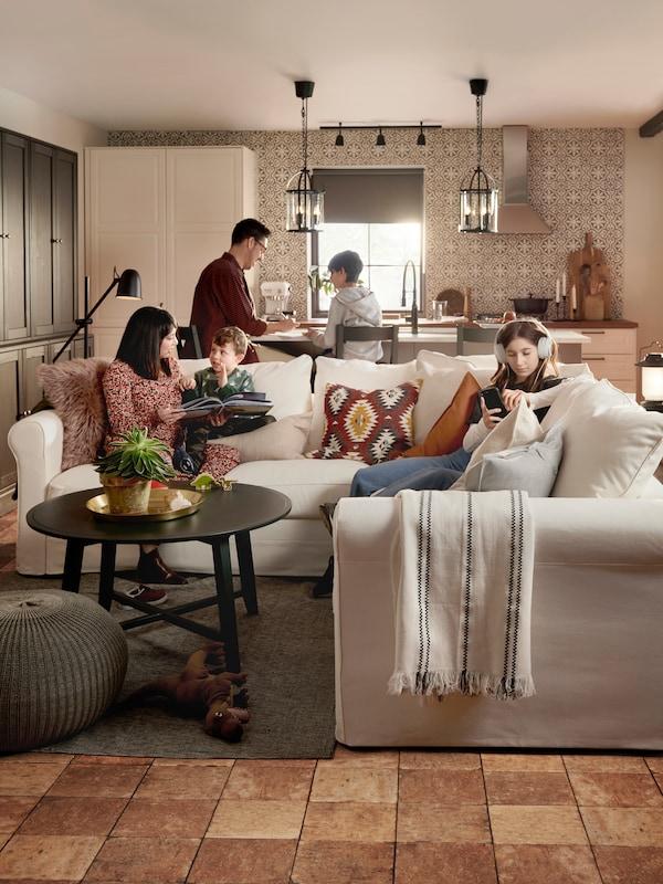 Rodina s dětmi v obývacím pokoji a hrají společně na hudební nístroje. Na stěně visí obrázky, na podlaze je barevný koberec